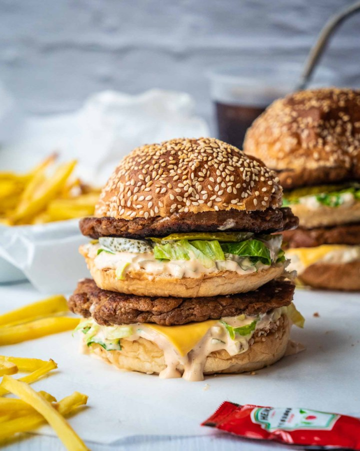 two vegan big macs filled with double seitan patties, burger sauce, pickles, vegan cheese slices in sesame buns in front of white brick wall