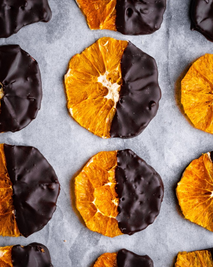 dehydrated orange crisp slices coated in chocolate laying in neat rows on a baking tray lined with greaseproof paper