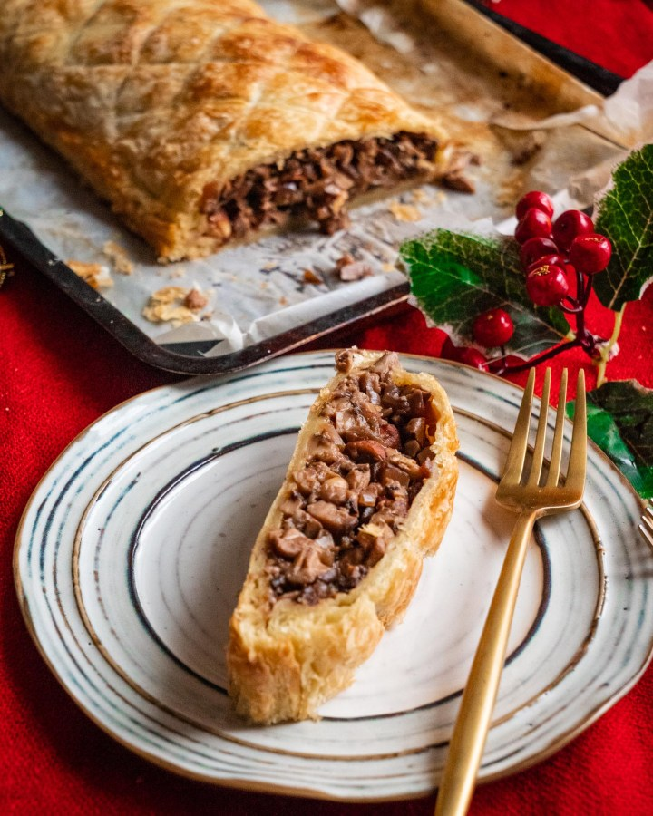 slice of filled puff pastry on white pottery plate next to entire rest of rectangular pie on red tablecloth decorated with holly