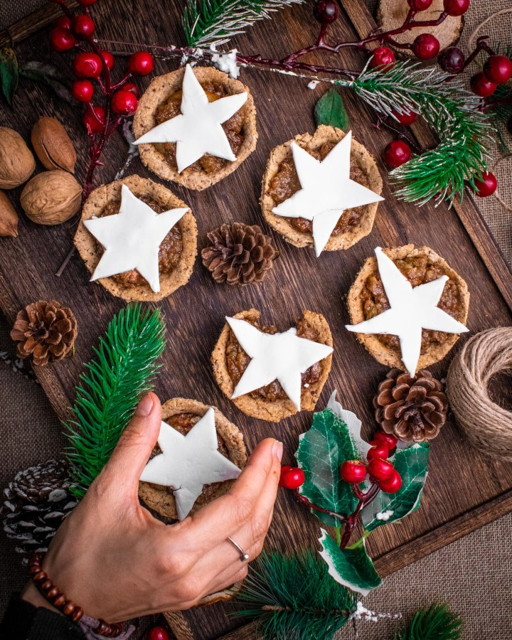 flatlay mince pies on wooden tray surrounded with green pine tree trimmings and red holly bush berries with hand taking one pie