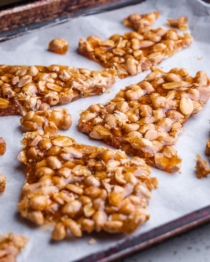 peanuts covered in crunchy golden caramel resting in shards on white tray