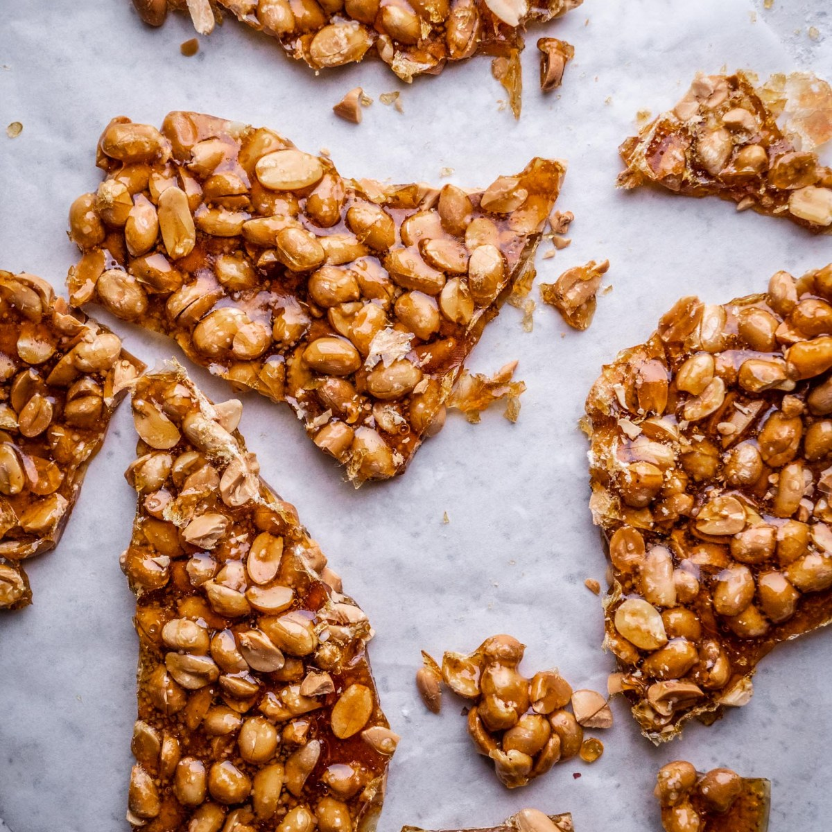 golden crunchy peanut brittle shards on tra lined with greaseproof paper