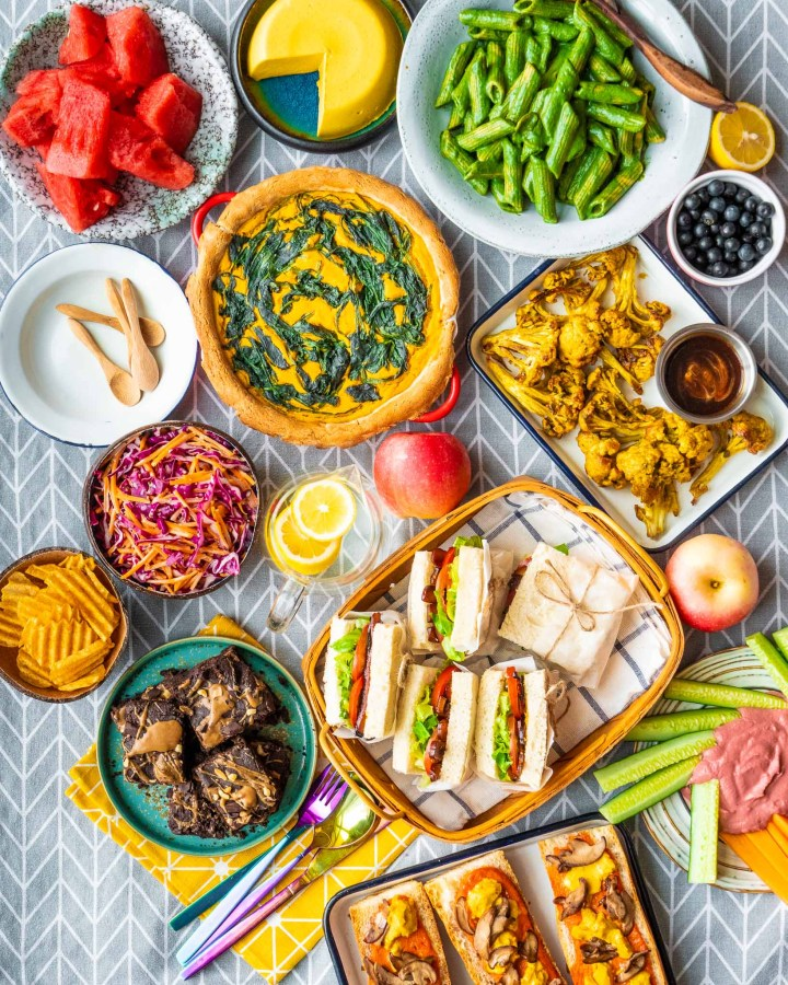 picnic spread flatlay laden with vegan quiche, pasta salad, sandwiches, fruit, dips, brownies and veg sticks