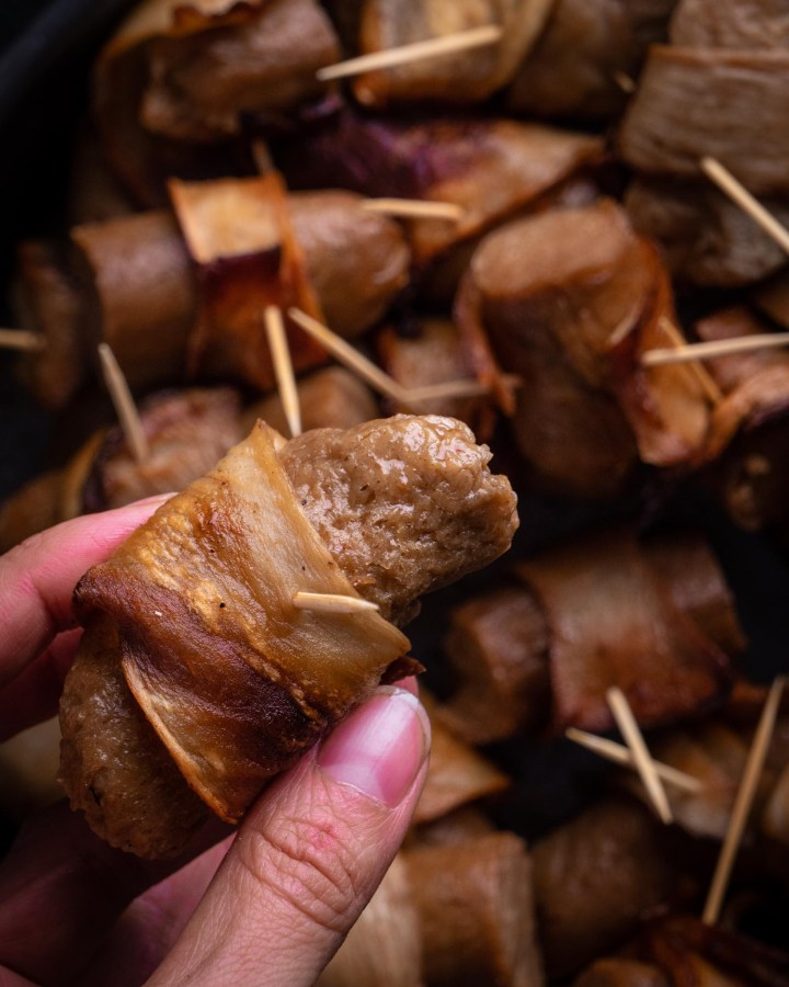 mini individual vegetarian pigs in blankets made with vegan sausages wrapped in vegan bacon