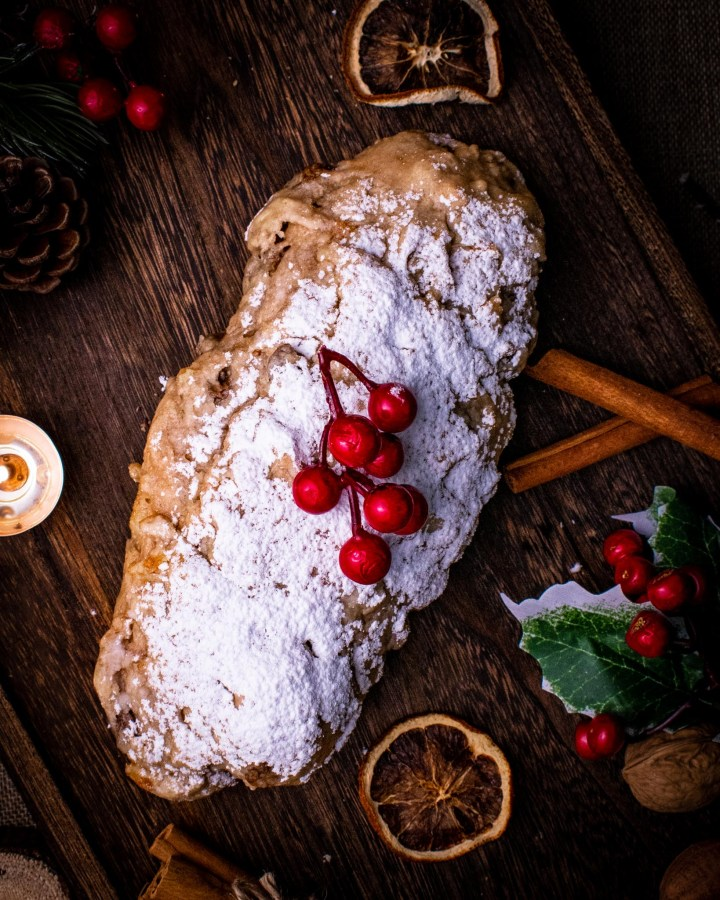 stollen dusted generously with icing sugar powder, red berries and dried orange slices next to cinnamon sticks, holly and candles