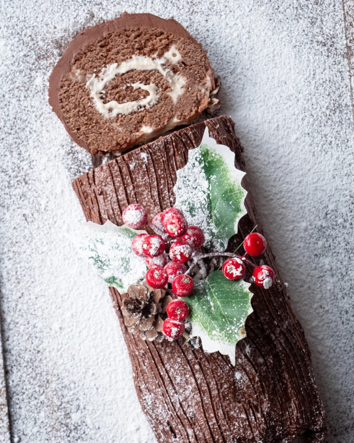 sliced swiss roll flat lay with chocolate sponge roll filled with swirls of vegan cream and dusted with powdered sugar and holly