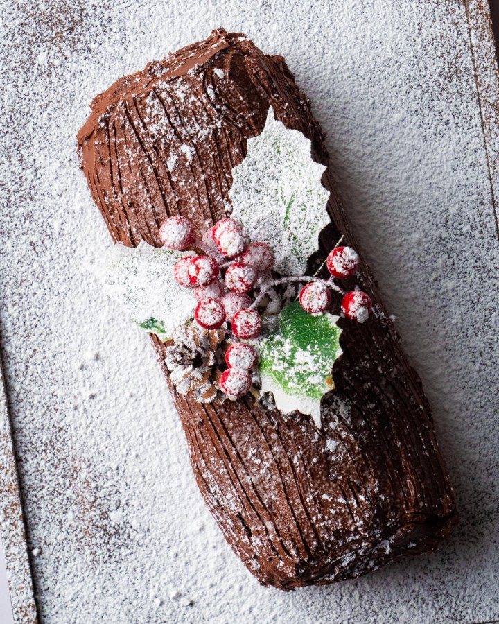 flatlay christmas chocolate swiss roll topped with holly sprigs and pinecones on snowy white surface