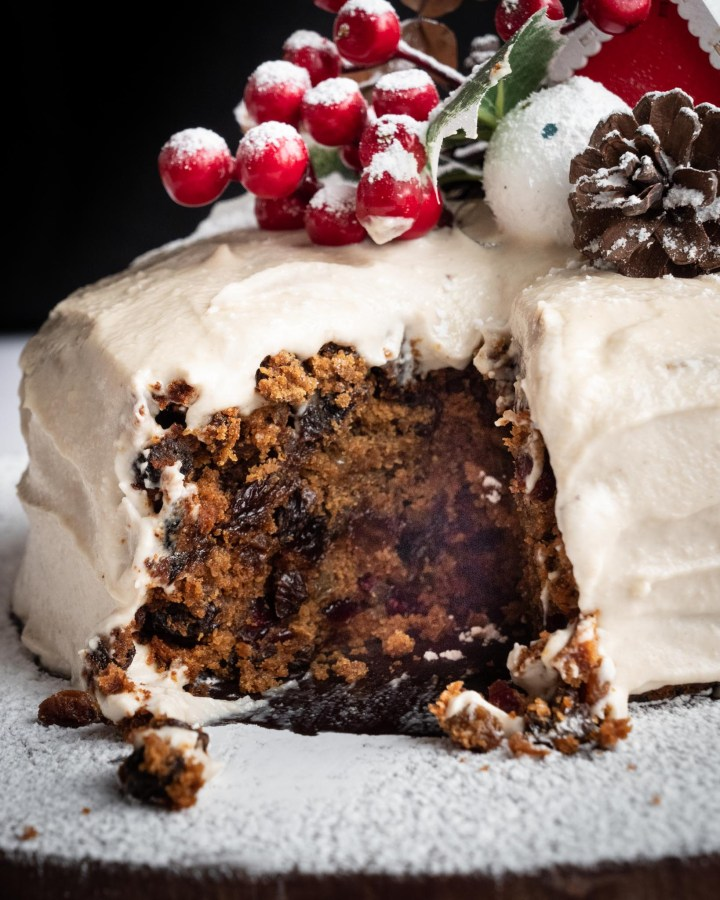 traditional christmas cake with slice taken out to reveal centre filled with brown and red fruits and topped with christmas decorations