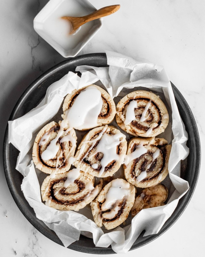 cinnamon rolls in round baking tin lined with white parchment paper on white marble table next to pot with wooden spoon dripping with icing