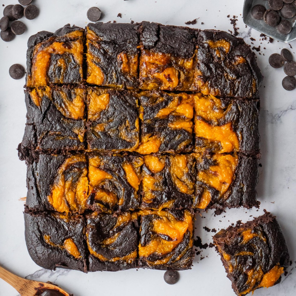 batch of brownies cut into squares topped with pretty pumpkin swirls and a chunk loosely sticking out
