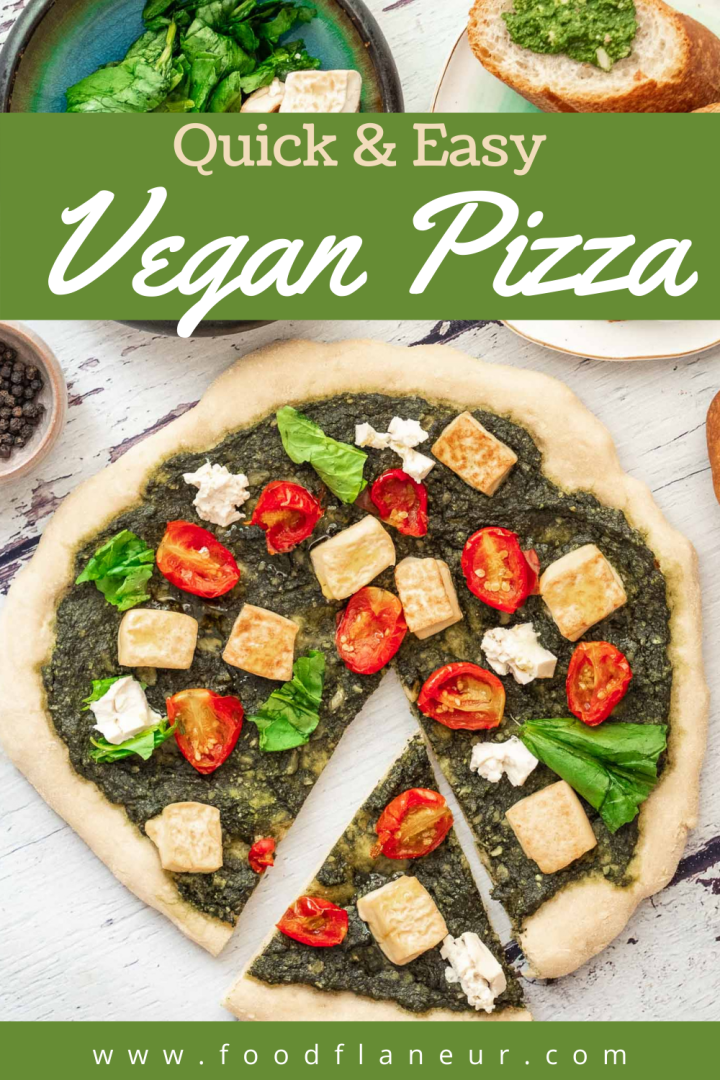 large vegan pizza topped with tofu chunks, tomatoes, basil and pesto on white marble table surrounded by sides