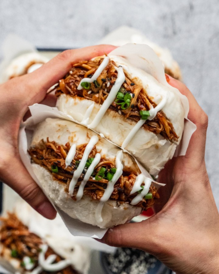 hands squeezing bao buns with filling coming out consisting of pulled mushrooms in sticky sauce