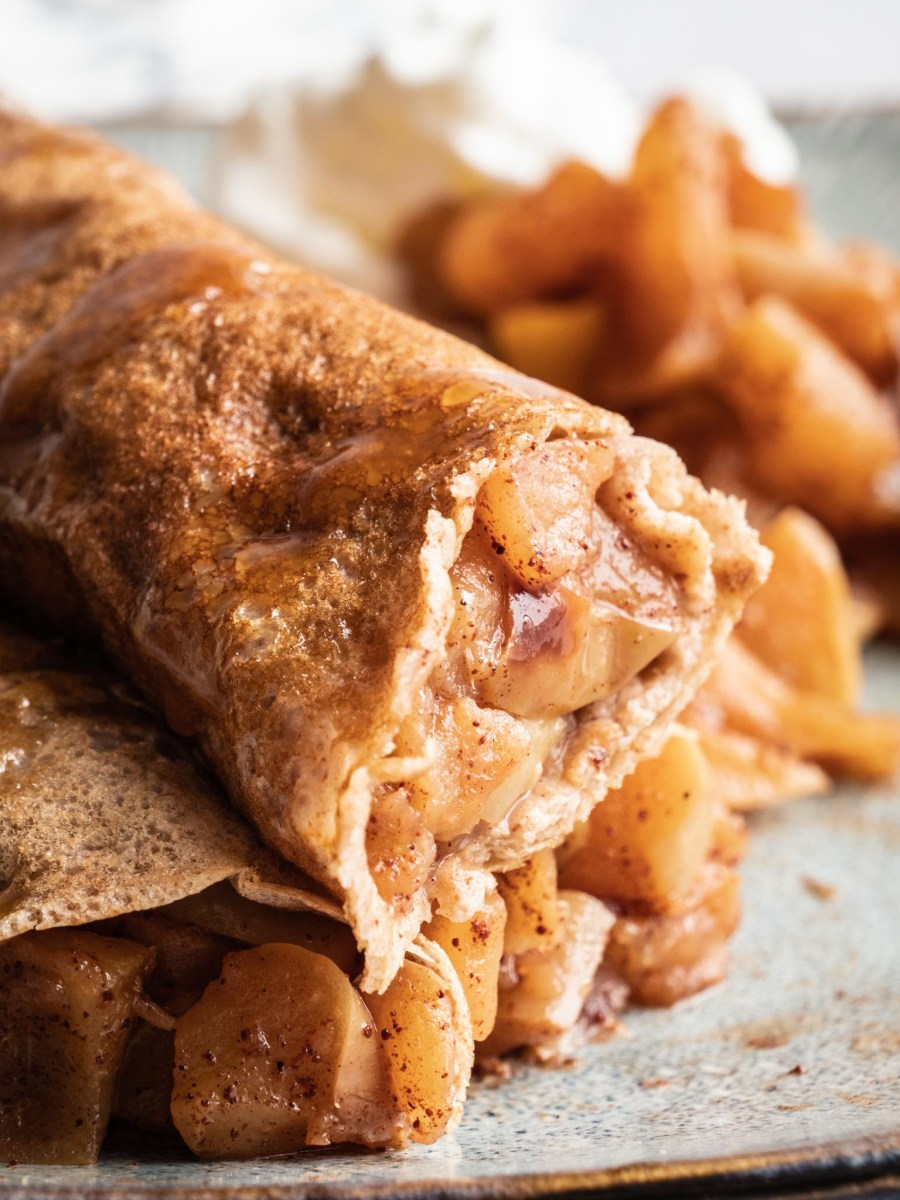 vegan cinnamon apples crepes rlled up and stacked on top of each other