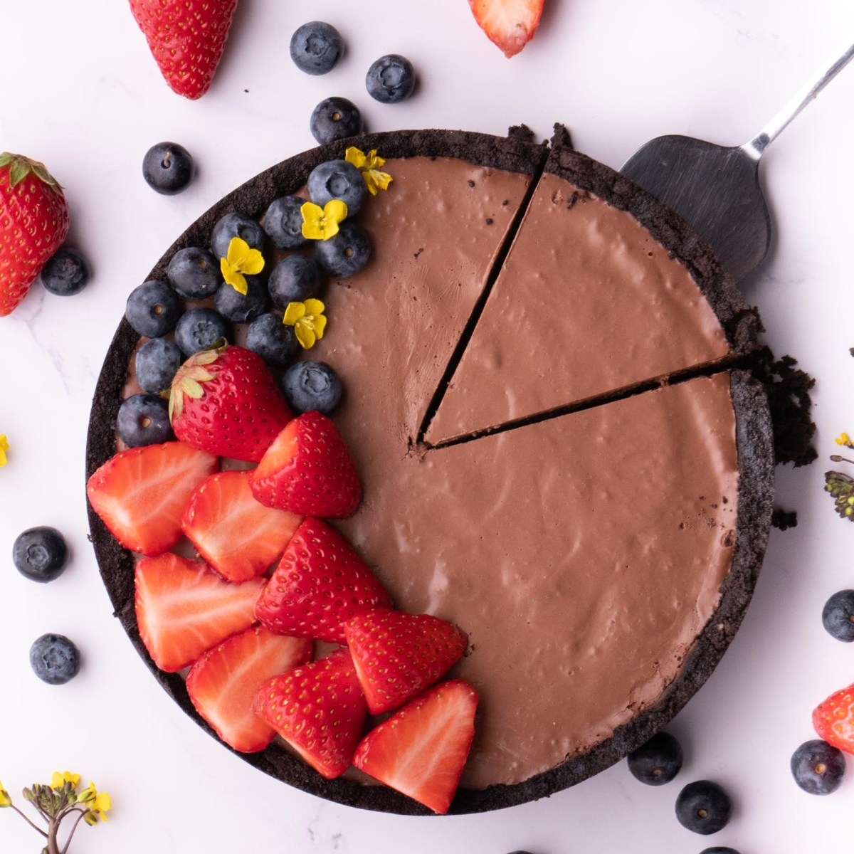round chocolate tart, with 1 slice cut decorated with berries and flowers