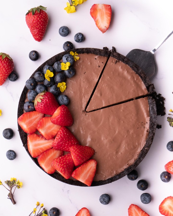 round chocolate tart topped on one side with strawberries, blueberries and yellow edible flowers with silver cake slice underneath triangle slice