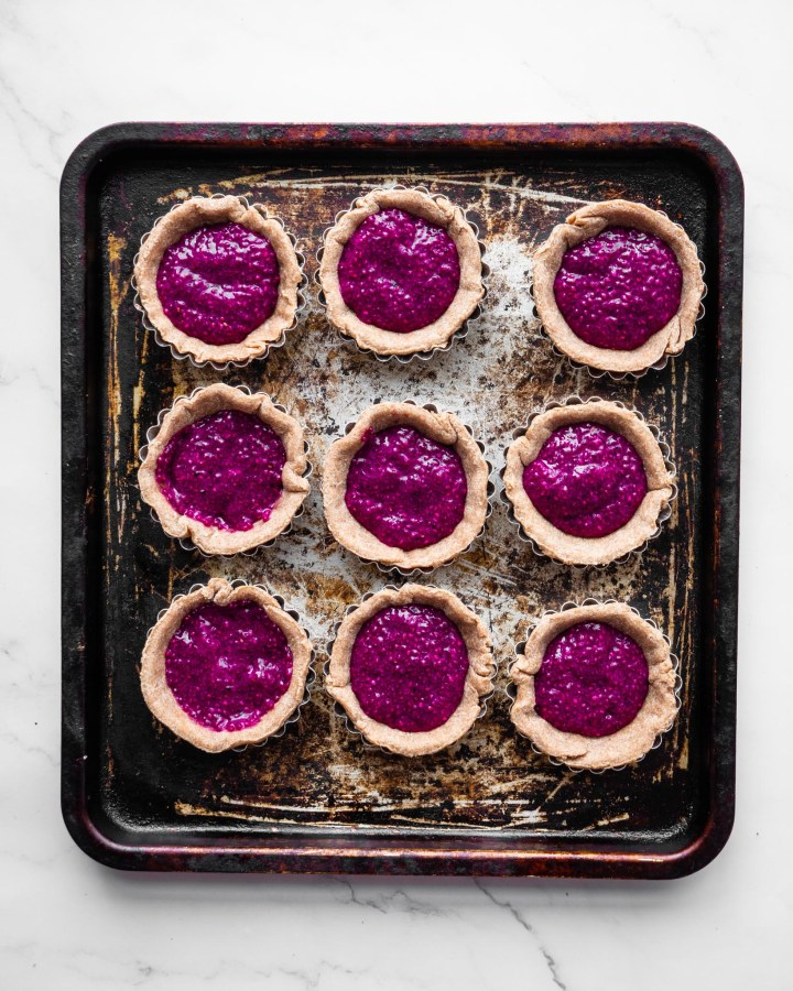 jam tarts on baking tray filled with pink jam