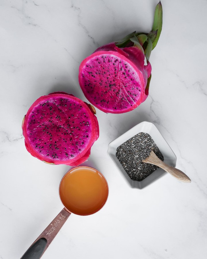ingredients for chia fruit jam with chia seeds in stoneware pot with wooden spoon, pink dragon fruit and orange juice in copper cup on white marble top