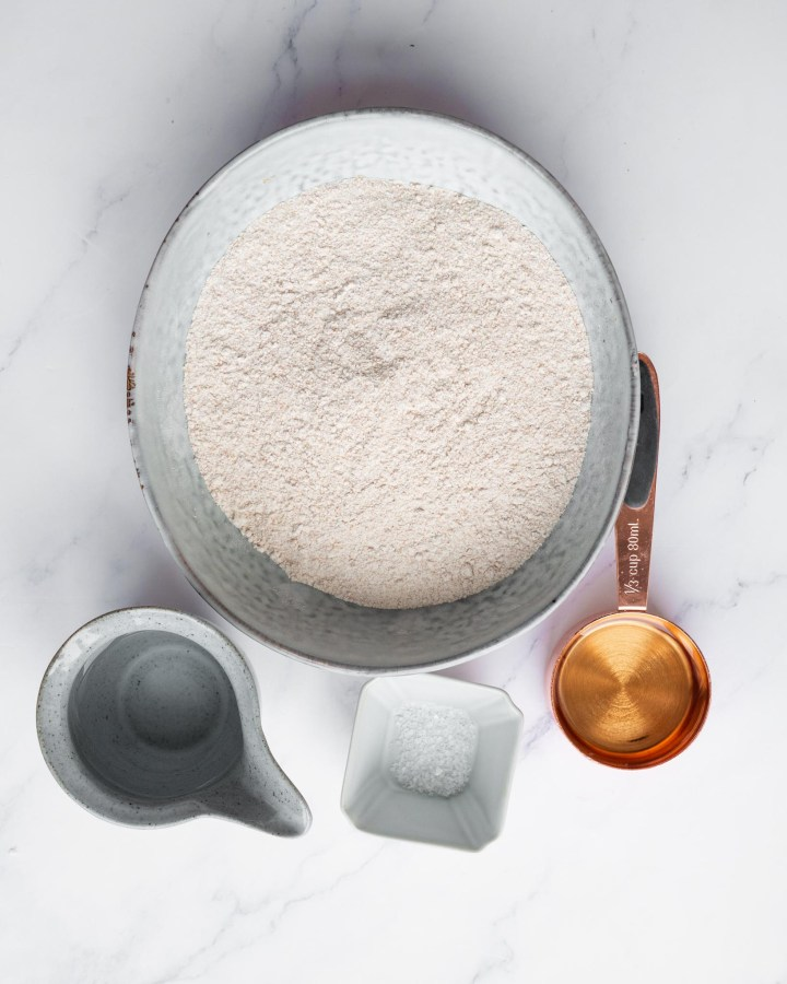 ingredients for jam tart step by step instructions with stoneware containing flour, copper pot with water and pottery cup with salt
