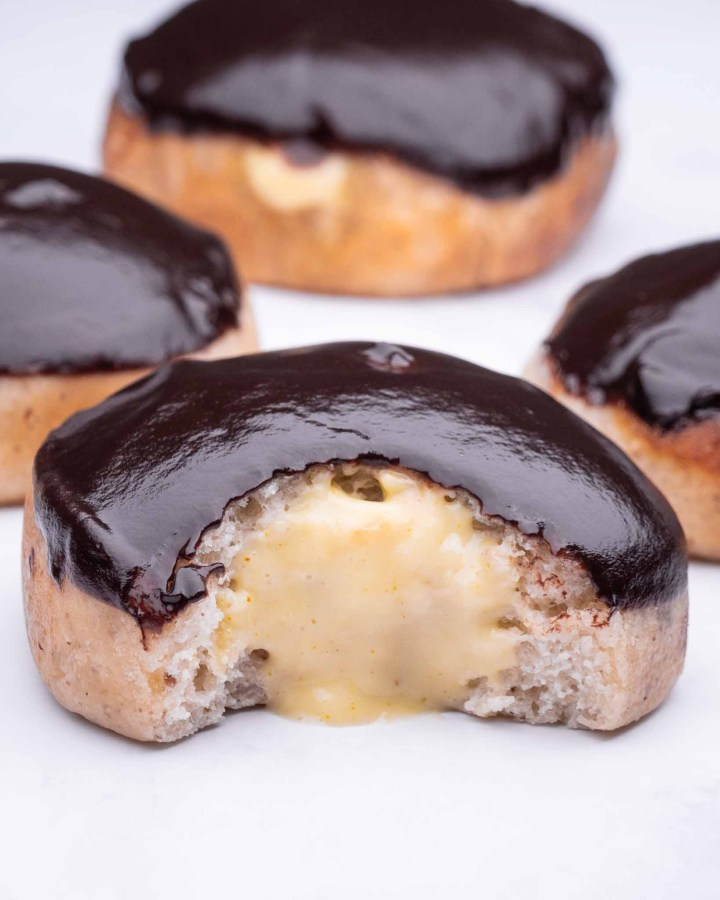 krispy kreme donut recipe with chocolate glazed doughnuts filled with vegan custard laid on tabletop and bite taken so custard oozing out