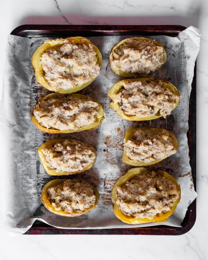 potato skins loaded with mashed potato and mushrooms laid neatly in rows on baking tray lined with greaseproof paper