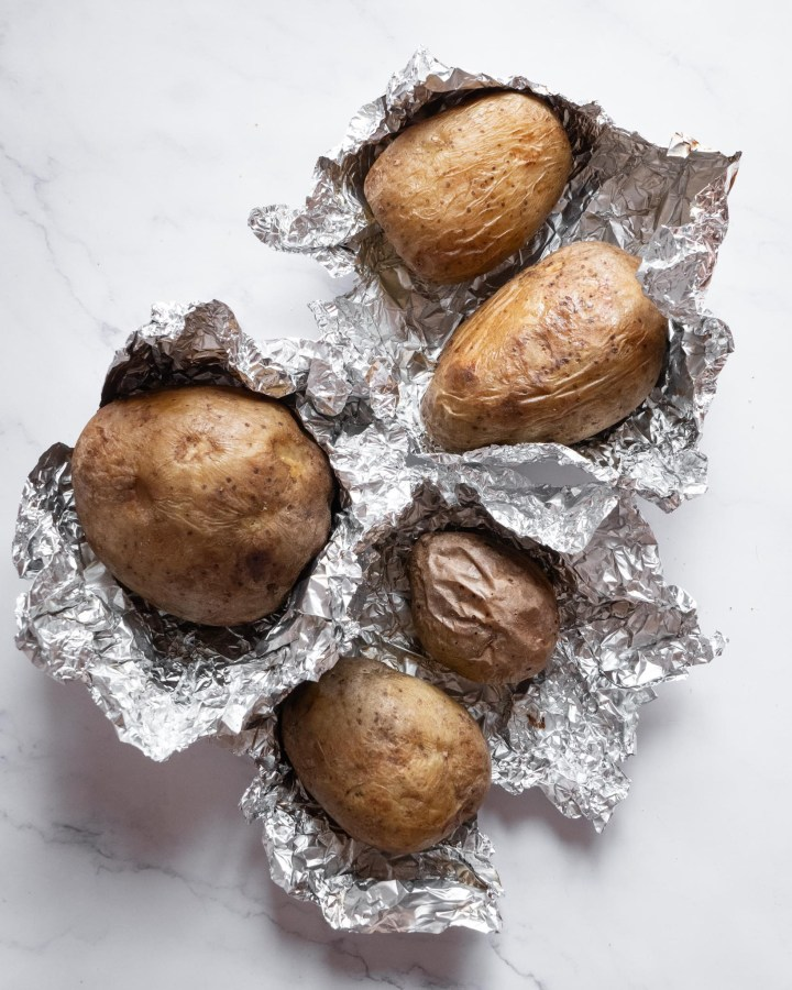 flatlay whole baked potatoes in foil, half unwrapped on white marble surface