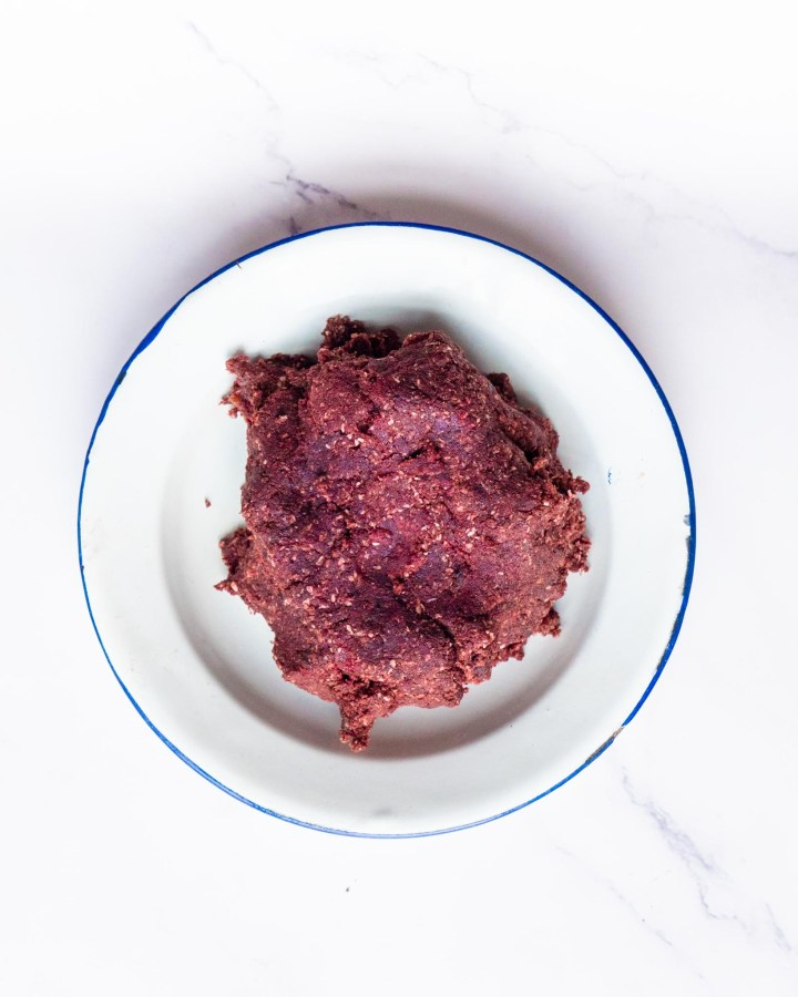 purple red velvet cake protein ball batter in rustic white enamel plate