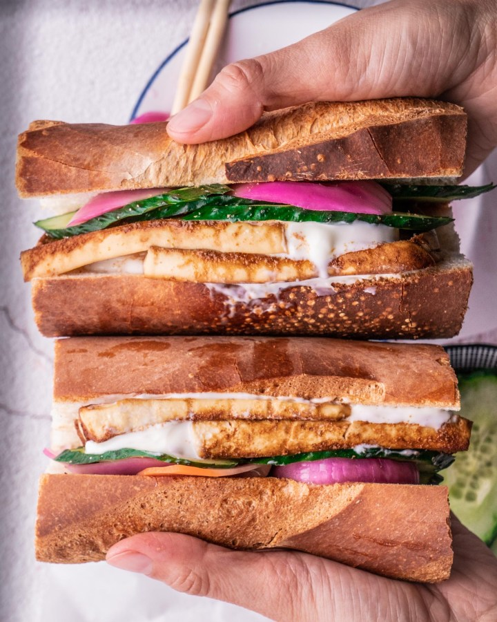 hands holding stack of vegan banh mi sandwich baguettes stuffed generously with sticky tofu chunks, pink pickled onions and cucumber