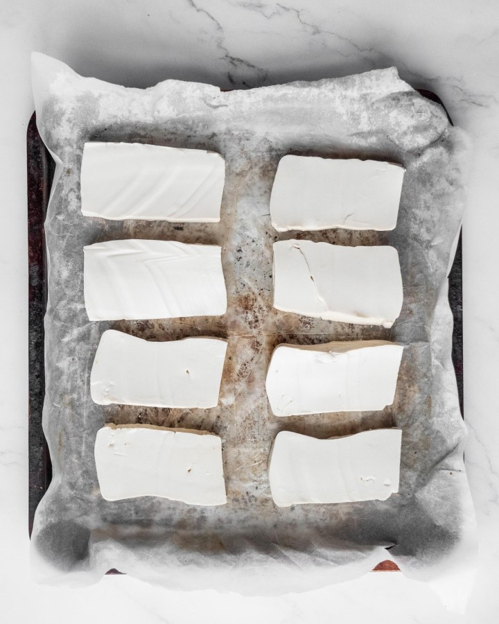 rectangular slices of firm tofu laid neatly on baking tray lined with greaseproof paper for step by step cooking instructions
