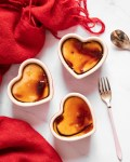 3 vegan creme brulees in red heart shaped ramekins on white marble table surrounded with crumpled red cloth and gold spoons