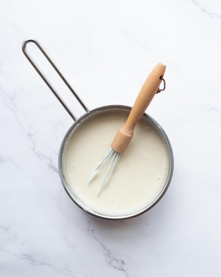 vegan custard in saucepan with whisk on white marble table to show step by step instructions for making custard