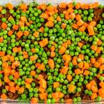 Sprinkle peas and carrots on top of beef mixture.