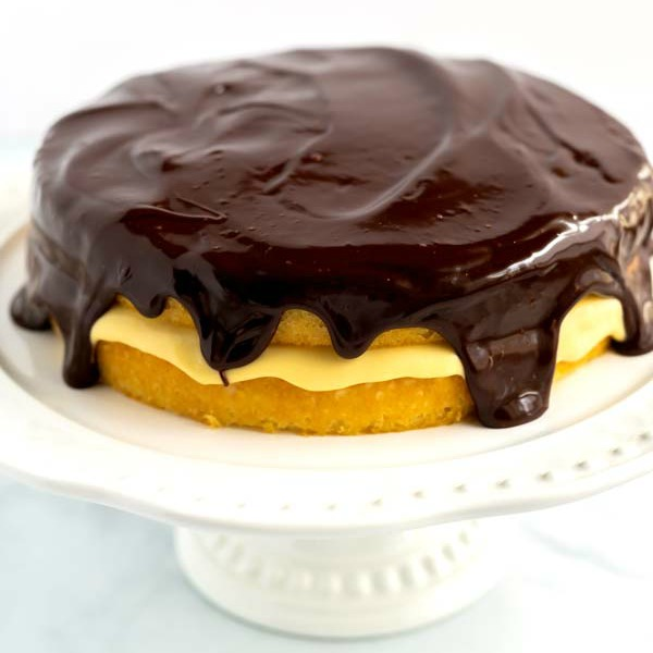 Cake on a cake stand covered in chocolate ganache.
