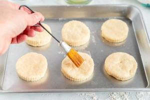 Brush the dough rounds with egg white and sprinkle with sugar.