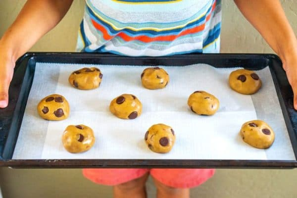 5-year old holding a backing sheet with cookie dough ready for the oven.