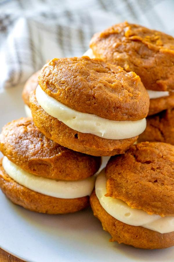 A plate of pumpkin whoopie pies stacked on top of each other.