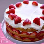 A layered strawberry cream cake on a cake stand with text overlay for Pinterest