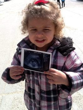 Mia holding a picture of her soon-to-be little brother or sister.
