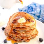 Buttermilk Buckwheat pancakes with syrup being poured over them.