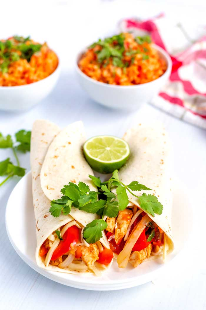 Two chicken fajitas rolled up on a plate with fresh lime.