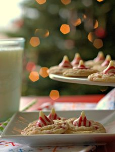 Peppermint cookies on a white plate with a lit Christmas tree in the background.