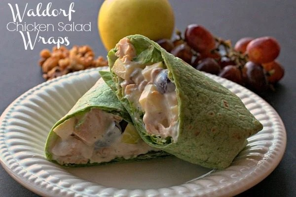 A sliced Waldorf Chicken Salad Wrap on a white plate.