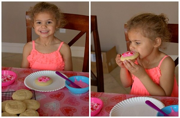 Child frosting sugar cookies and decorating them.