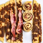 Place a piece of bacon onto each strip of dough and roll in buns.