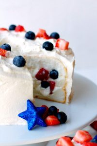 This Patriotic Tunnel Cake is a quick and easy dessert for Memorial Day, 4th of July, Labor Day, or anytime! It's filled with fresh whipped cream, strawberries, and blueberries!