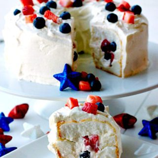 A slice of Patriotic Tunnel Cake on a plate with the remaining cake in the background on a cake stand