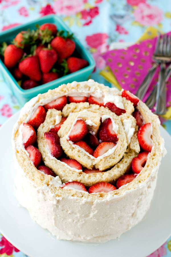 Roll Up cake with strawberries on a white cake pedestal.