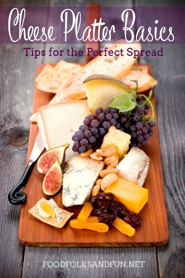 Cheese board with cheese and fruits on it with text overlay for Pinterest