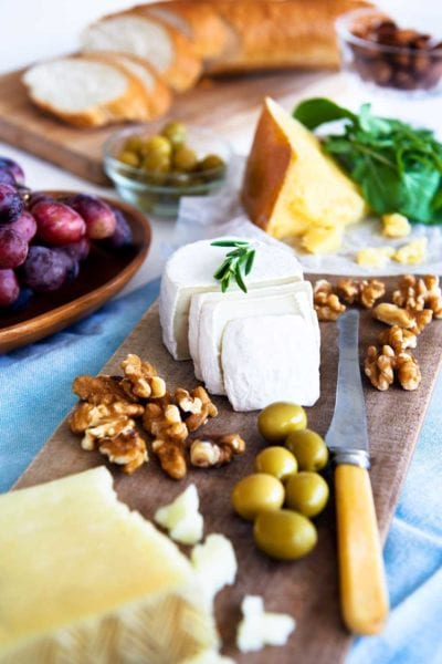 cheese, nuts, and olives on a wooden board.