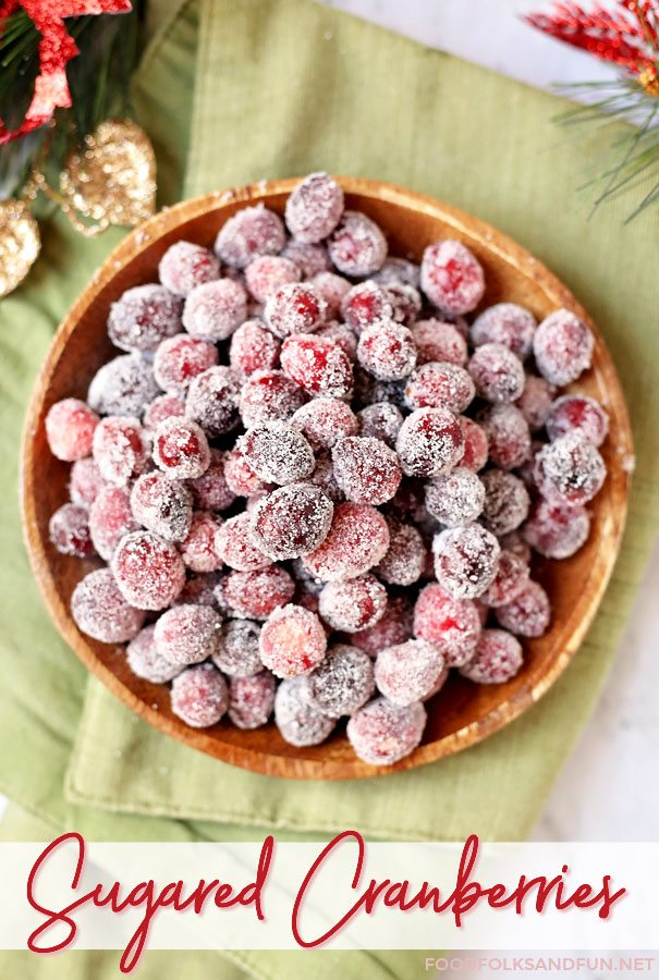 An overhead picture of frosted cranberries in a wooden bowl.