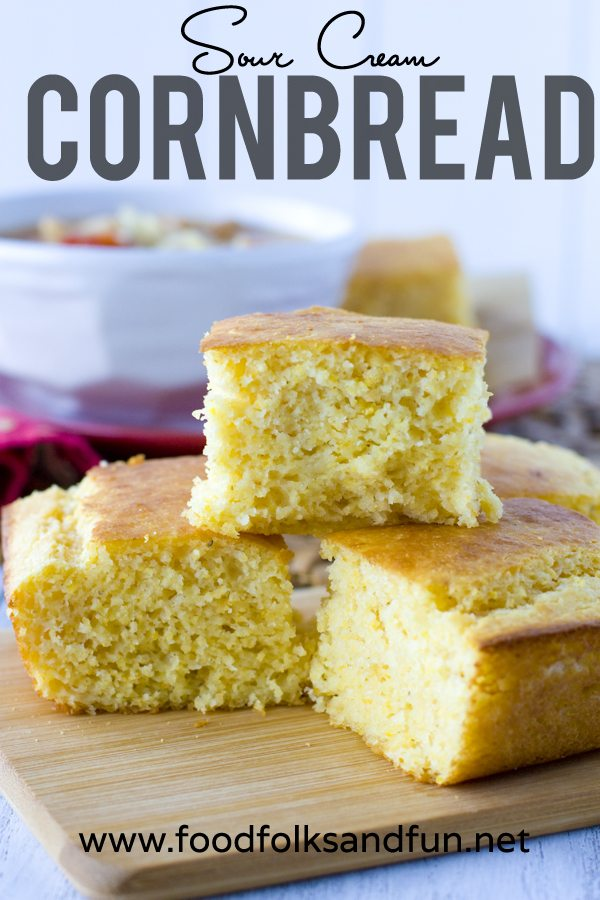 Sour Cream Corn Bread stacked on a wood cutting board.